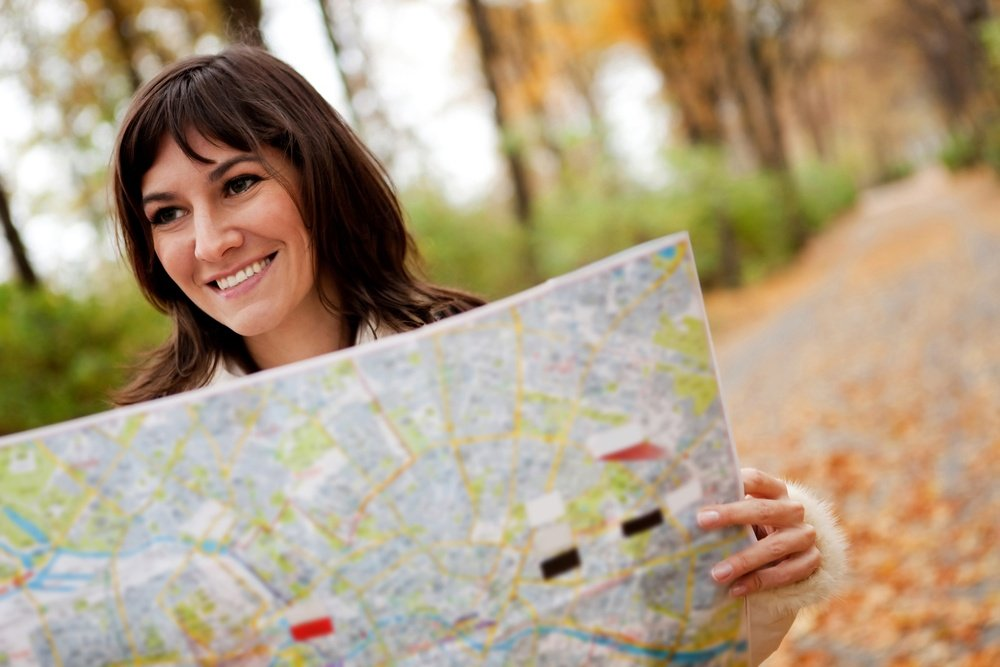 Woman sightseeing outdoors and holding a map